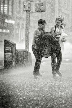 Фото Парень с девушкой под ливневым дождем на улице города пытаются открыть зонт