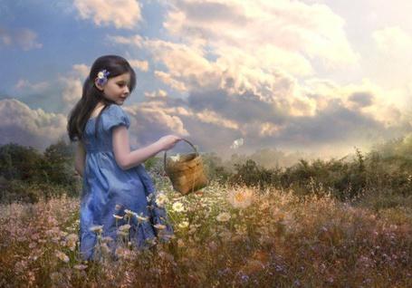 Фото Девочка в синем платье с корзинкой, на которой сидит бабочка, гуляет по цветочной поляне