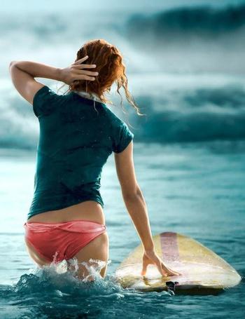 Фото Мокрая девушка с доской для серфинга идет к волне