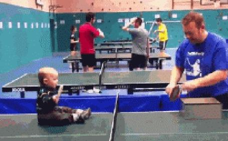 Фото Маленький мальчик играет в натольный теннис сидя на столе
