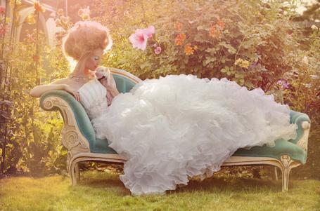 Фото Девушка в пышном белом платье лежит на диване на улице