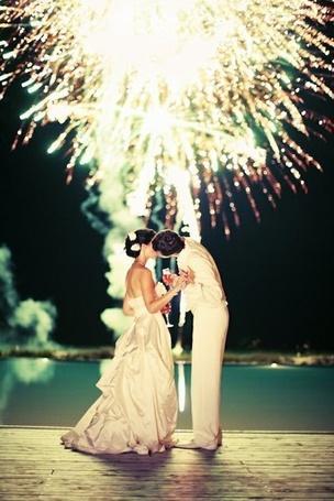 Фото Жених и невеста с бокалами в руках целуются на фоне фейерверка