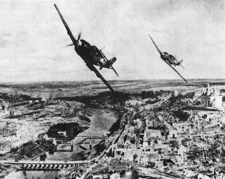 Фото Пара немецких истребителей Мессершмитт Bf.109 / Messershmitt Bf.109 пролетает над разрушенным  городом Смоленском