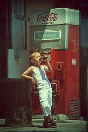 Фото Американский мальчик пьет из бутылки напиток Кока-Колу / Coca Cola на фоне автомата по продаже напитка, фото 50-х годов прошлого века
