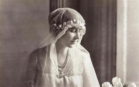 Фото Элизабет Боуз-Лайон / Lady Elizabeth Bowes-Lyon  супруга короля Георга VI и королева-консорт Соединённого Королевства сидит грустная смотря на цветы