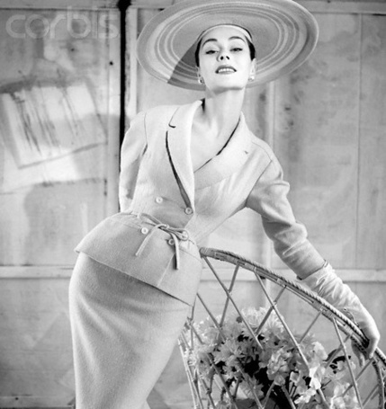 Фото Девушка в шляпе облокотилась на плетённое кресло с цветами. 50-ые годы 20-го века. Фотограф Henry Clarke  для журнала Vogue