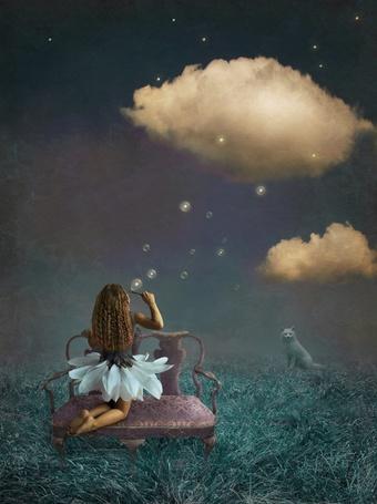 Фото Девочка на диване стоящем в поле пускает мыльные пузыри ночью