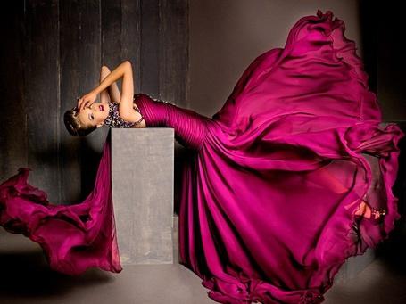 Фото Девушка в вишневом платье легла на прямоугольный блок