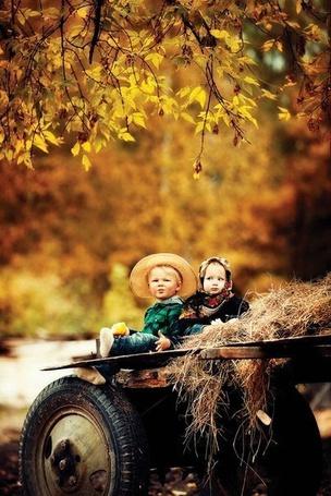 Фото Мальчик и девочка сидят на тележке с сеном
