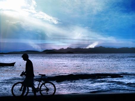 Фото Мальчик, идущий с велосипедом по берегу озера