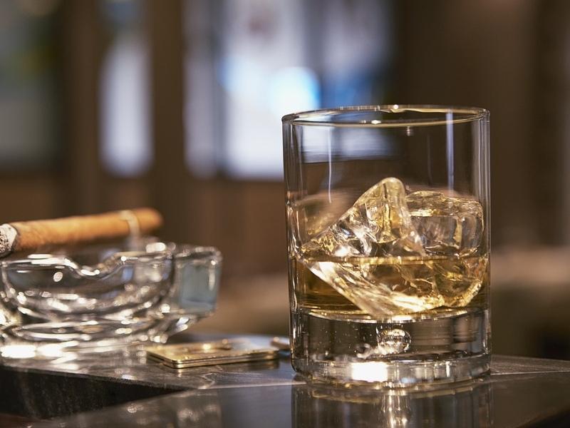 Фото На барной стойке стоит стакан виски со льдом, пепельница с лежащей на ней сигарой