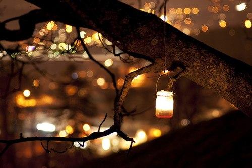 Фото Баночка с горящей в ней свечой висит на дереве