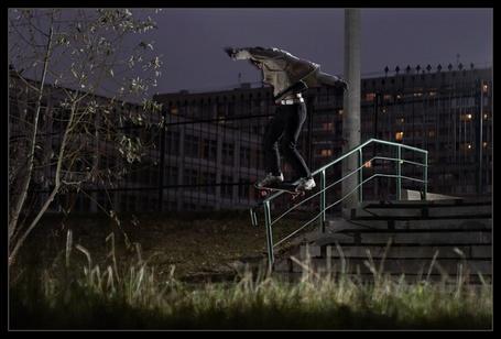Фото Юноша на скейтбординге совершает ночную прогулку по перилам лестницы