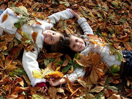Фото Две девочки-подружки, сцепившись руками, лежат на осенних листьях