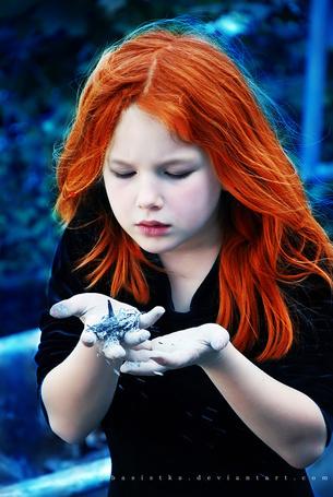 Фото Рыжеволосая девочка сдувает с руки голубой пепел