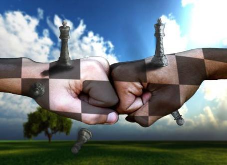 Фото Две руки на фоне природы, изображающие шахматную доску с фигурками королей на кулаках