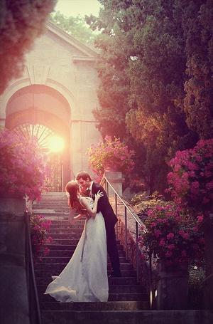 Фото Жених и невеста целуются на лестнице перед аркой