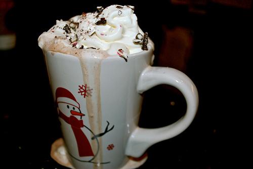 Фото Кружка горячего шоколадного напитка со взбитыми сливками и нарисованным снеговиком
