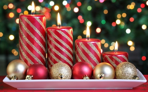 Фото Свечи стоят в ряд рядом с новогодними игрушками