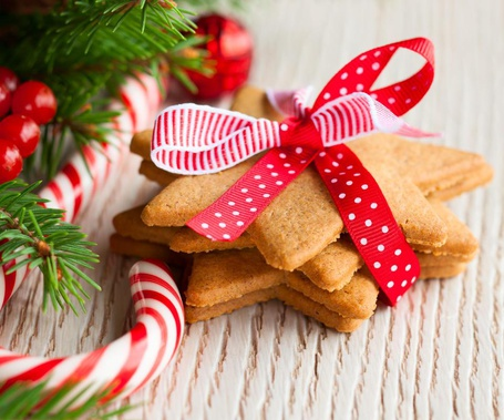 Фото Новогодние сладости, состоящие из печенья и леденцов, а также еловая ветка, красные шарики