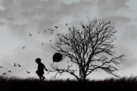 Фото Мальчик с воздушным шариком возле дерева без листвы
