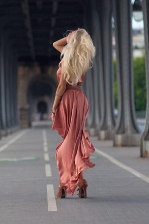 Фото Девушка в длинном платье стоит взяв себя за лицо подняв голову в верх