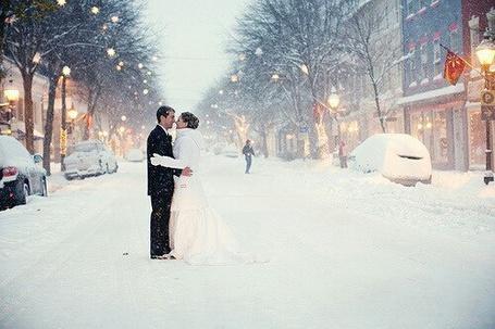 Фото Мужчина с девушкой зимой стоят посредине улицы