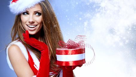 Фото Красивая девушка-шатенка в костюме Снегурочки с новогодним подарком