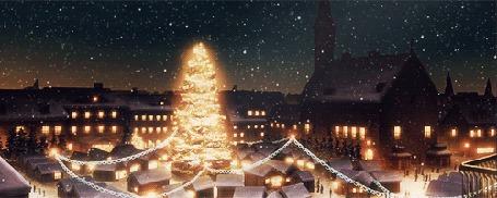 Фото Светящаяся новогодняя елка на городской площади, снег опускается на город