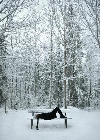 Фото Девушка лежит на лавочке на фоне заснежных деревьев