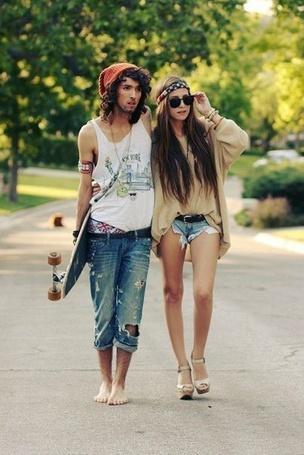 Фото Мужчина со скейтом идёт в обнимку с девушкой по тротуару