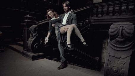 Фото Мужчина поднимается по лестнице со спящей девушкой на руках, в руке у девушки, одетой в медицинскую перчатку, находится шприц