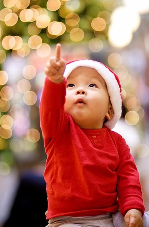 Фото Удивленный маленький мальчишка в шапочке Деда Мороза показывает пальчиком на огоньки