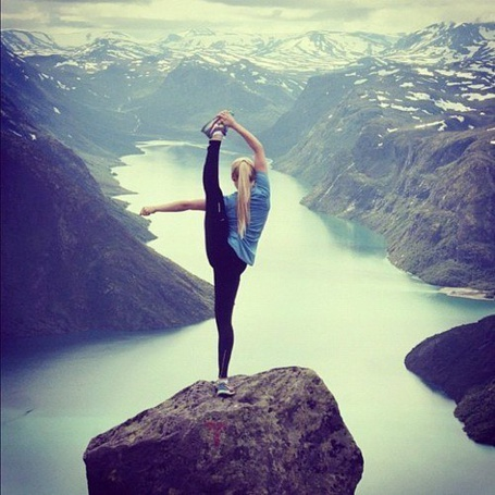 Фото Девушка стоит на краю скалы с поднятой в шпагат ногой
