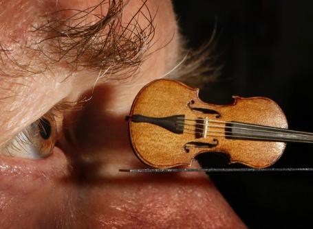 Фото Маленькая скрипочка лежит напротив мужского глаза