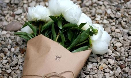 Фото Букет красивых белых пионов, лежащих в бумажном кульке на гальке, с надписью 'WITH LOVE' / 'C любовью'