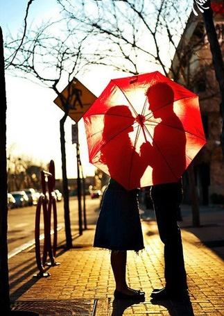 Фото Парень с девушкой стоят на улице прикрываясь красным зонтиком