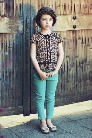 Фото Маленькая девочка в леопардовой кофте и бирюзовых джинсах стоит спиной к деревянным воротам (© ), добавлено: 31.12.2012 01:09