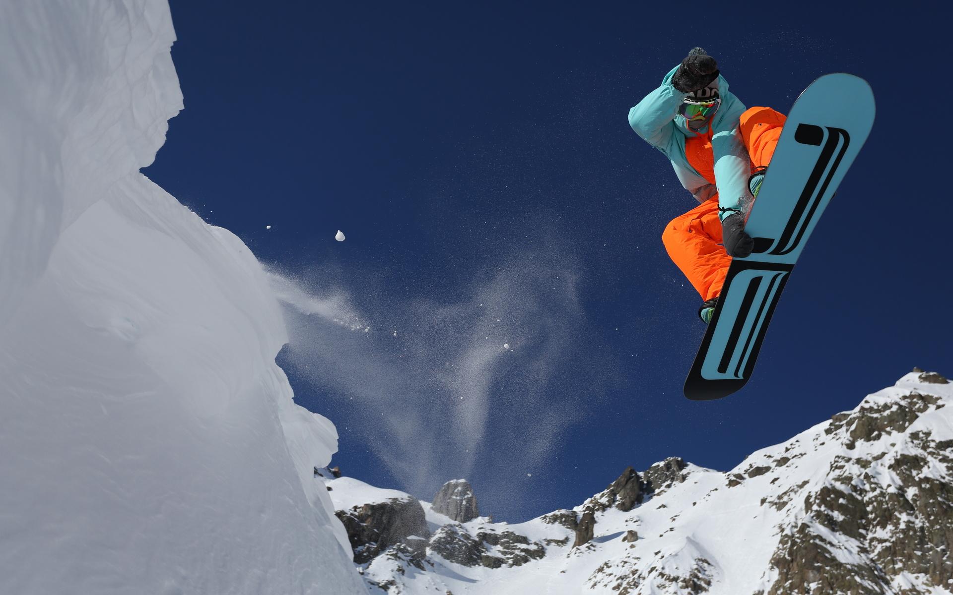 Фото Сноубордист в красивом прыжке на снежном склоне горы