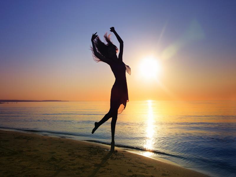 Девушка, встречающая рассвет на берегу моря
