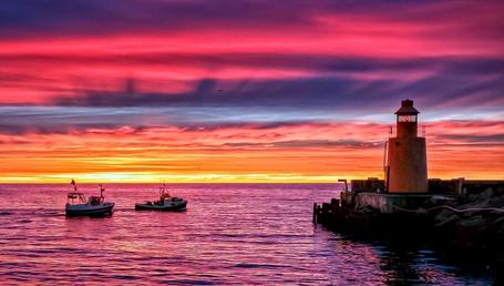 Фото Маяк, стоящий на морском пирсе на фоне желто-багряного заката солнца, недалеко от берега стоит пара небольших катеров (© Felikc), добавлено: 02.01.2013 11:31