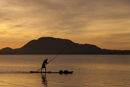 Фото Туземец плывёт на пироге по океану