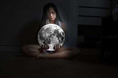Фото Девушка сидит посреди комнаты с луной в руках