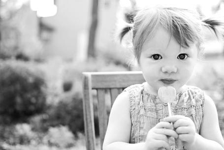 Фото Девочка с большими чёрными глазами сидит на стуле с чупа-чупсом в руках