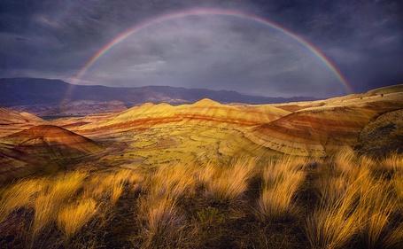 Фото Красивый вид горных образований на фоне дугообразной радуги, работа фотографа Марка Адамуса / Marc Adamus