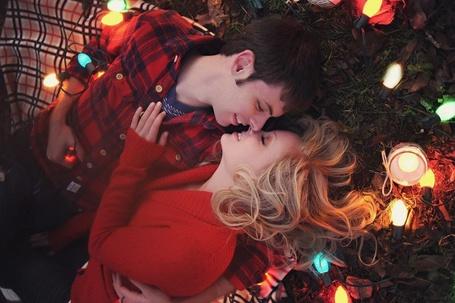 Фото Девушка с парнем лежат на подстилке и нежно касаются носами друг друга, вокруг них лежит новогодняя зажжённая гирлянда