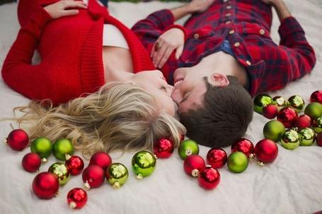 Фото Девушка с парнем лежат на спине и нежно касаются друг друга носами, их окружают новогодние игрушки