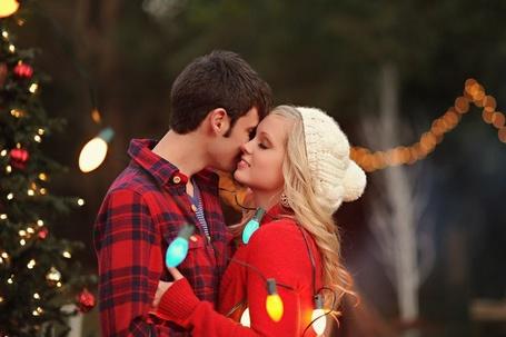 Фото Девушка с парнем обмотавшись новогодней гирляндой обнимаются рядом с наряженной ёлкой