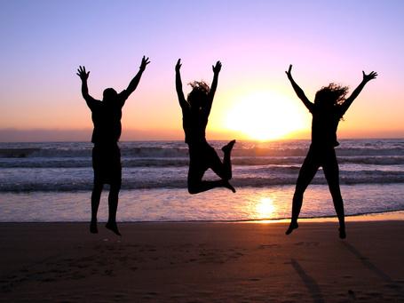 Фото Силуэты двух девушек и парня на фоне заката солнца над морем