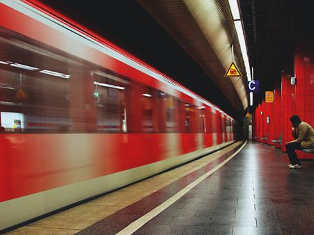 Фото Грустный, одинокий мужчина, сидящий на перроне железнодорожного вокзала, провожает взглядом уходящий пассажирский поезд